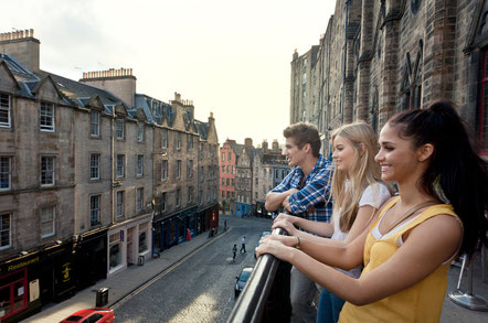 grassmarket-a-historic-street-in-edinburgh-three-young-people-on-the-terrace-overlooking-the-street-and-terraced-houses